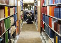 Northwestern Health Sciences University student in the library stacks
