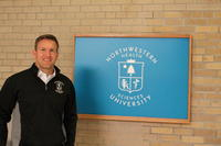 Northwestern Health Sciences University alum in front of university sign